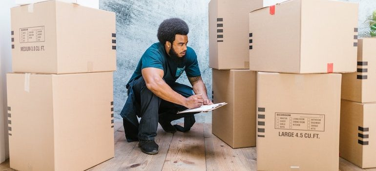 man making notes on a clipboard surrounded by boxes