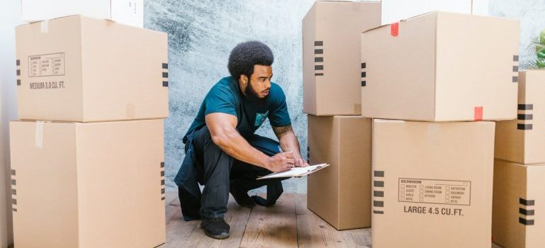 A man among moving boxes writing in a notepad