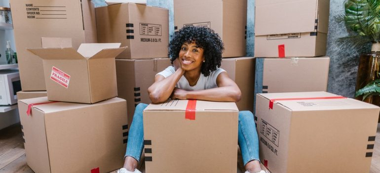 A smiling woman surrounded by moving boxes