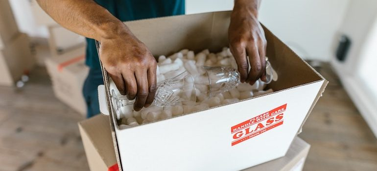 hands putting glasses into a box