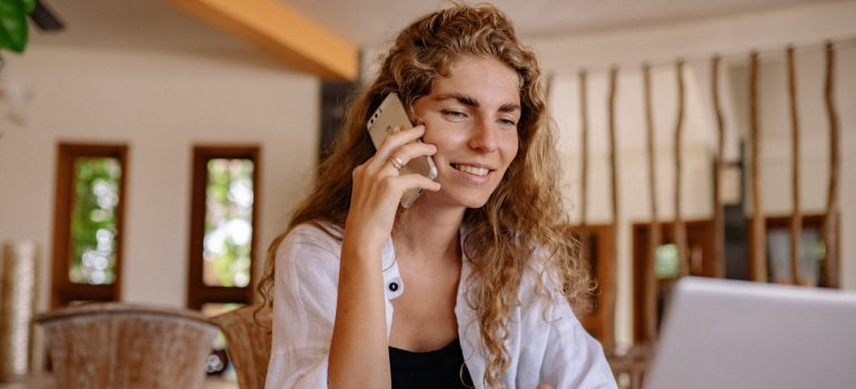 Woman using phone to ask for a binding moving estimate.
