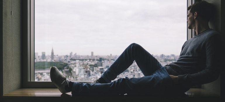 A man sitting on a window sill.
