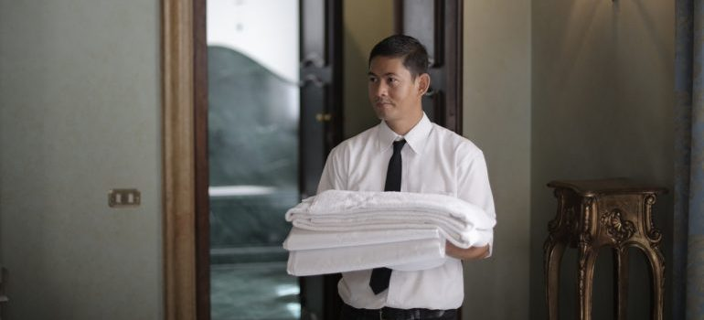 A man preparing to propperly store away sheets and bedding.