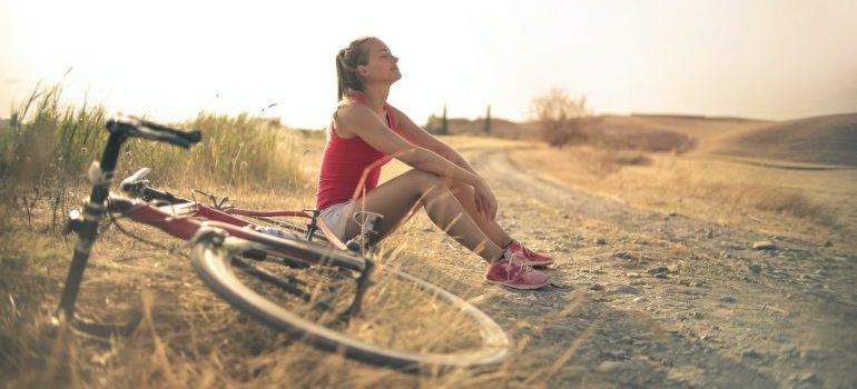 A girl resting next to her bike.