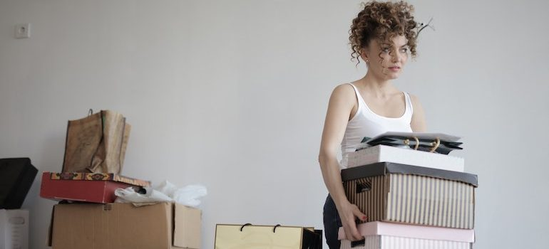 woman carrying boxes surrounded by boxes