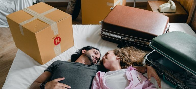 A young couple lying on a bed among suitcases.