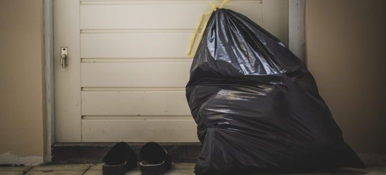 A black trash bag and slippers near the door.