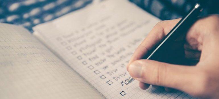 A person creating a checklist for a less stressful move.