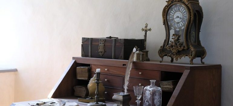 A small grandfather clock on an antique desk.