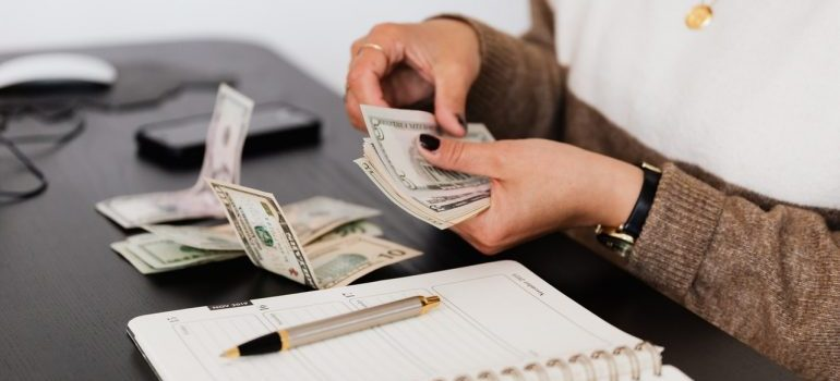 A person sitting at a table with a stack of banknotes and a planner